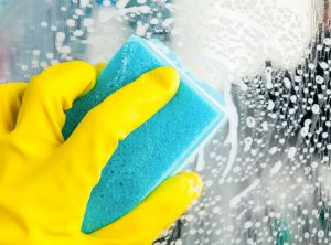 A person using a cleaning product and sponge to wash glass.