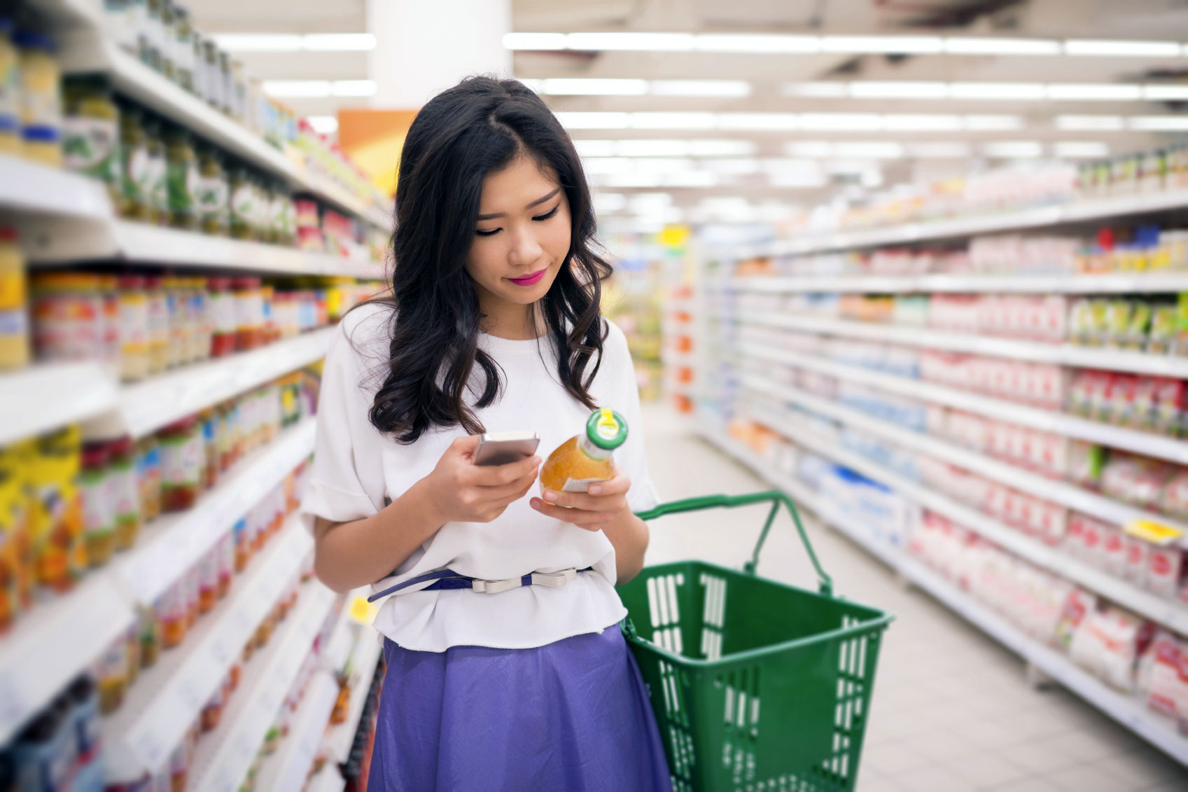 woman holding orange juice while grocery shopping