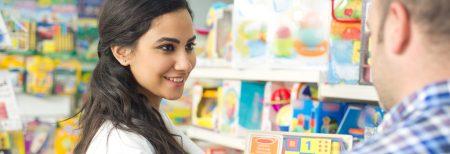 Frau, die sich in der Spielzeugabteilung eines Ladens mit einem Mann unterhält
