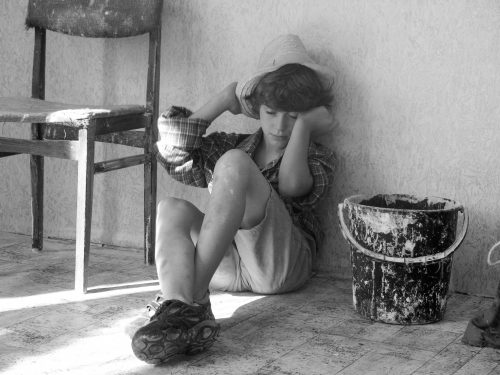 Child labour concept. Tired boy painter is very tired after work. Black and white photo.