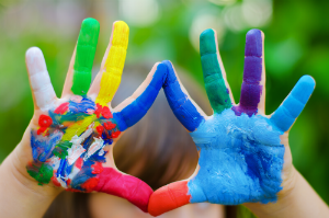 Child's hands painted in different bright colors