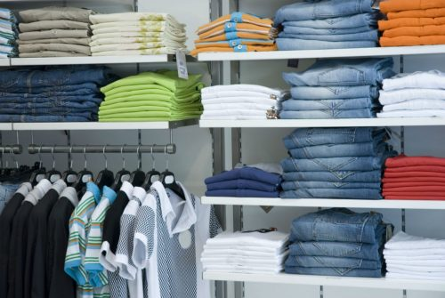 clothes on a rack and shelves in a store