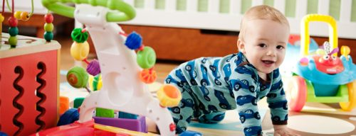 baby crawling on floor, surrounded by toys