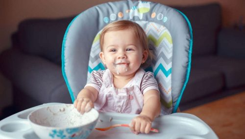 Portrait of cute adorable Caucasian child kid girl sitting in high chair eating cereal with spoon.