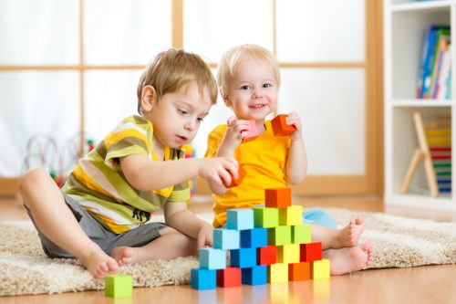 Preschooler children playing with colorful toy blocks.