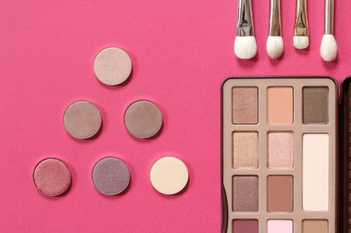 Set for trendy natural eye makeup. Palette of eye shadow in gold tones, makeup brushes. Top view on a pink background.