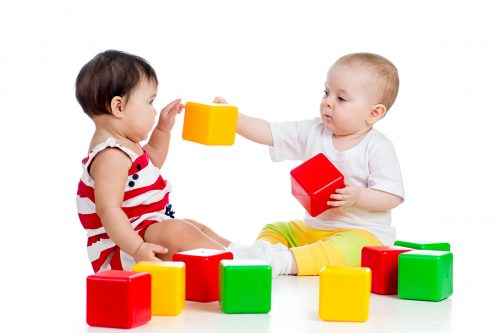 two babies playing together with colored blocks