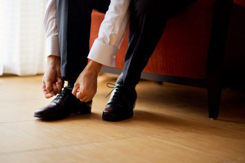 man in business attire, tying shoe
