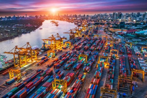 The image is of a shipping yard at sunset