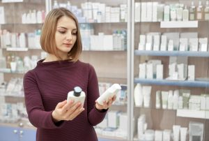 Cutomer choosing medical products for health care and wellbeing. Beautiful woman thinking, holding two white cosmetic bottles in hands. Woman standing in drugstore.